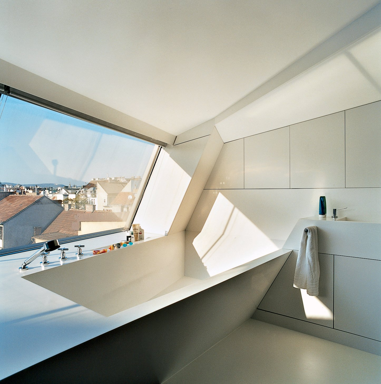 The cavity for the bathtub is part of the same continuous form-world as House Ray 1's sloping roofscape. The white tub is made from Corian; the faucet is by Dornbracht.  Photo 5 of 16 in The Penthouse Has Landed