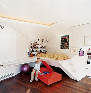 Nora, the architects' six-year-old daughter, hangs out next to her built-in bed.