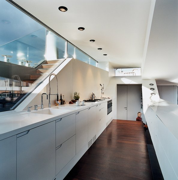 The kitchen window looks out to stairs that lead up to a small roof terrace. The kitchen faucet is byDornbracht. The recessed lighting is by Guzzini.