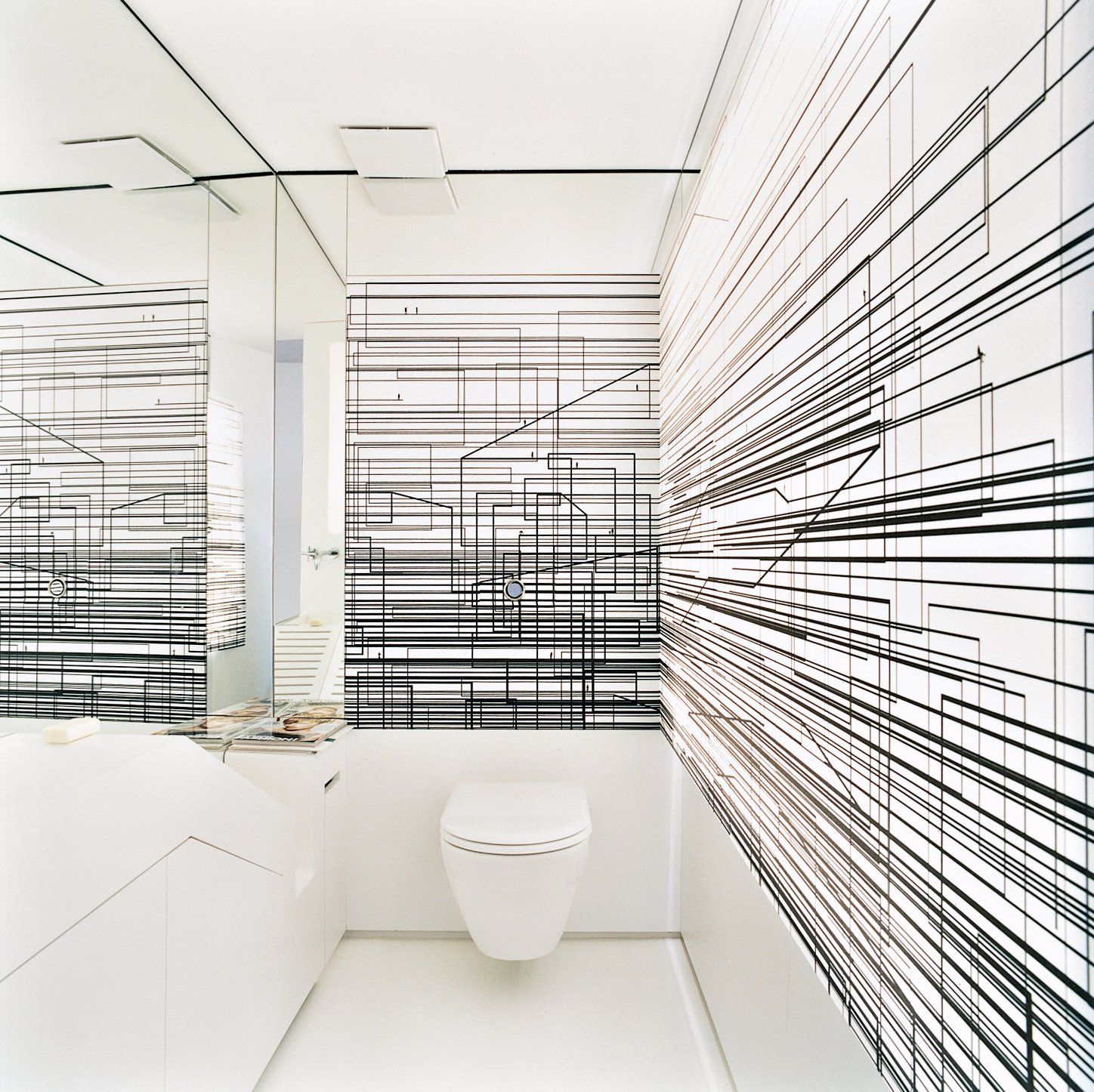 The walls of the toilet room are decorated with an abstract composition of overlapping black lines printed on a screen that is lit from behind.  Photo 12 of 16 in The Penthouse Has Landed