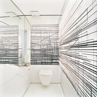 The walls of the toilet room are decorated with an abstract composition of overlapping black lines printed on a screen that is lit from behind.