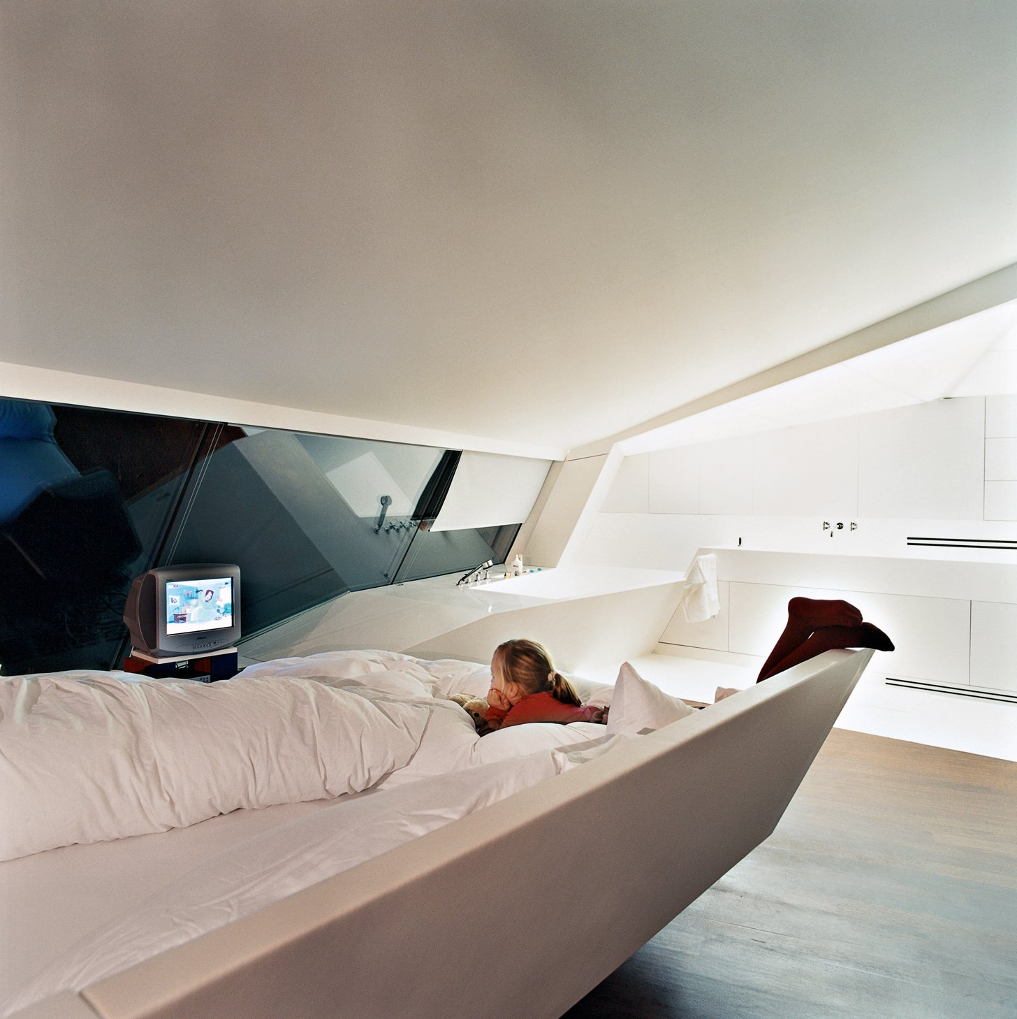 Converging lines of sheer glass, sloping floors, and ceiling planes create the impression of multiple perspectives and vanishing points. There are no interior walls except for those around the bedrooms (as seen here, in the master).