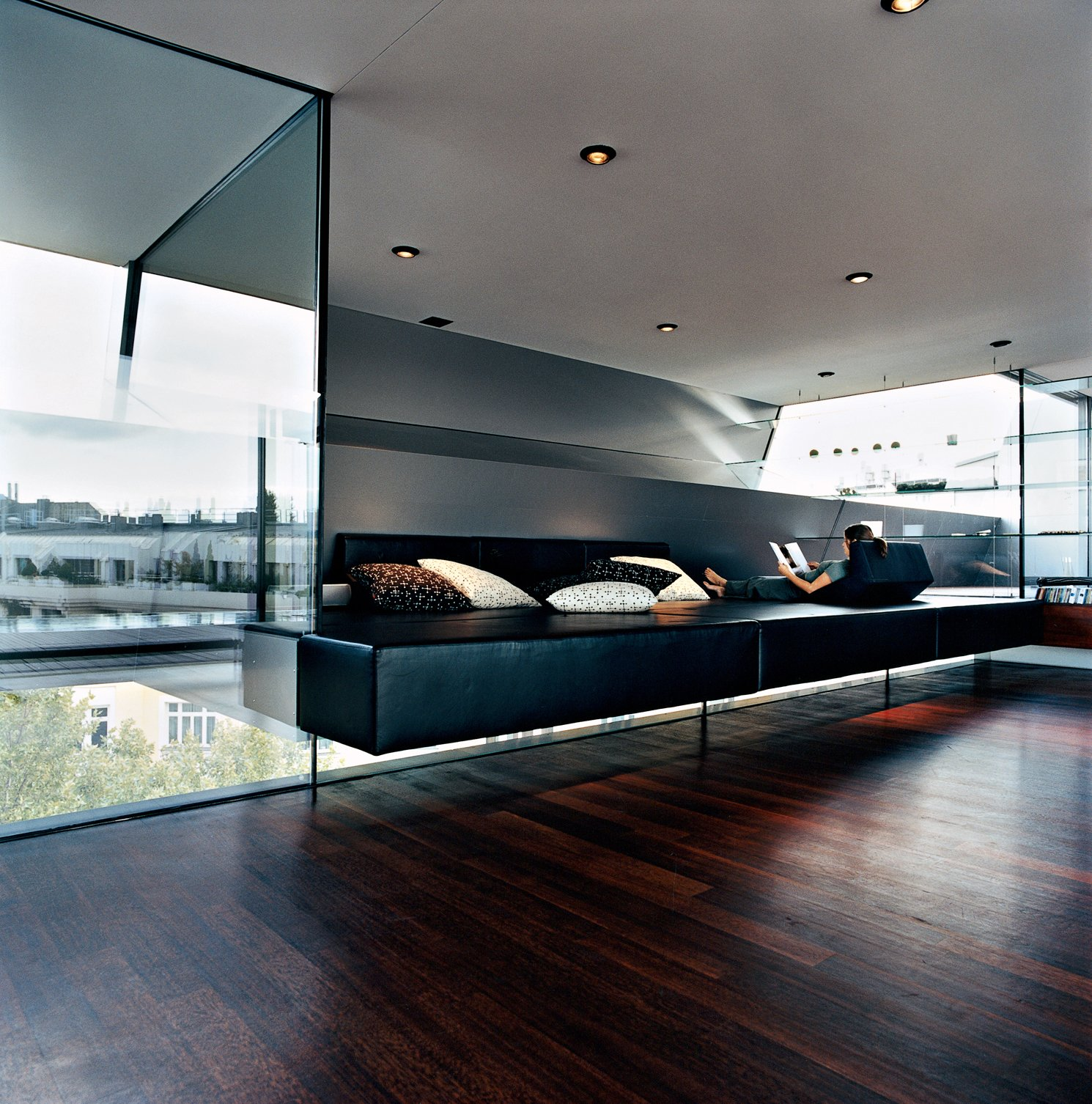 """Meissl and Delugan's favorite part of the house is definitely the """"relaxation zone,"""" which features a black leather plaform of their own design that appears to float between layers of tempered glass. The pillows are by Herman Miller.  Photo 16 of 16 in The Penthouse Has Landed"""