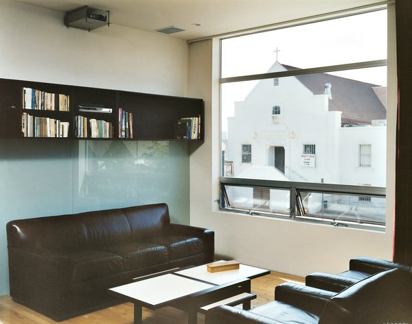 All the west-facing windows frame the church across the street. Bookcases, also designed by MS-31, line the back wall. When the chairs and couch from Restoration Hardware face each other, it's a cozy little living room. Turn the chairs around and it's a full theater complete with an 11-by-17-foot image projected on the wall.