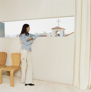 Making Sense of the City - Photo 10 of 11 - Maricarmen takes in the view from her and Sebastian's bedroom window, which frames the church's cross. White curtains and a flokati rug add a welcome layer of calmness in a house that's also home to their office and two young children.