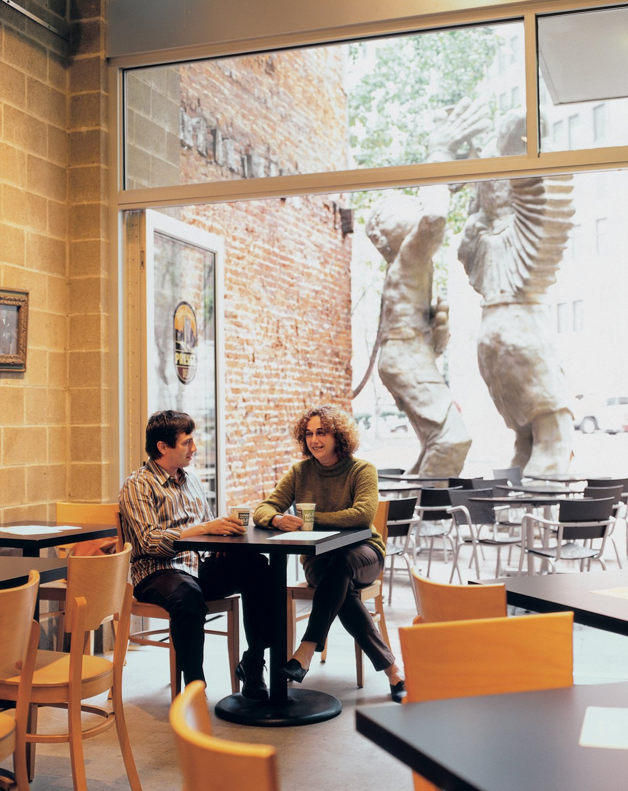 Architect Dutch MacDonald and developer Eve Picker relax at the Pittsburgh Presse Deli in the building's ground-floor storefront. De-signed by MacDonald's Edge Studio, the restaurant serves gourmet panini six days a week.