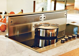 "Home Cooking - Photo 2 of 8 - Because the kitchen is so open, Erik designed it in such a way that there's room for everything from cookbooks to wine racks. Even the Viking stove hood disappears into the counter at the touch of a button. ""People ask if we spend a lot of time cleaning, but that's just not the case. There's a place for everything."""