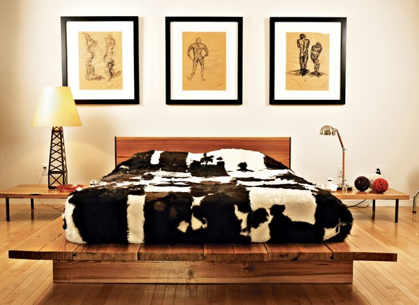 Graphic cowhides on the guest bed, the dining chairs, and the living room floor unite the varying levels of the house. That design element—and the cute oil derrick lamp in the guest bedroom—remind you that, yes, you are in Texas. The drawings are by Erik's brother Jair, an architect working in New York.