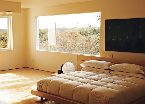 In the third-floor bedroom, horizontal wood-framed casement windows by Pella open out to tree-filled views of Lake Austin and Westlake Hills. Comfortably austere, the only furniture here is the bed, two nightstands, and a marble table for books and candles. Erik designed the bed, nightstands, and marble table; the paintings are by Jair.