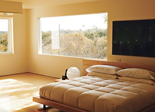 Home Cooking - Photo 4 of 8 - In the third-floor bedroom, horizontal wood-framed casement windows by Pella open out to tree-filled views of Lake Austin and Westlake Hills. Comfortably austere, the only furniture here is the bed, two nightstands, and a marble table for books and candles. Erik designed the bed, nightstands, and marble table; the paintings are by Jair.