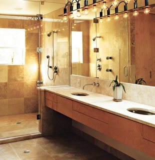 "Home Cooking - Photo 6 of 8 - The master bath is a simple rectangle. ""Like the kitchen, I designed it so that no stuff was laying around,"" Erik said. The surfaces are natural and subdued; a simple palette of tones, colors, and materials unifies the space. Travertine marble was used on the floors, shower, and countertop. The closet and cabinetry are maple. Erik designed the light fixture himself because, he says, ""there was nothing I could find that fit the scale of the room."" He used cold-rolled steel with exposed wires to give it an industrial feel."