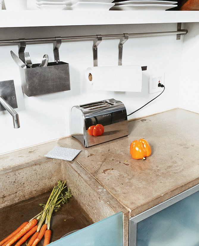 The cast-concrete sink, glass detailing, and steel appliances add to the clean, minimal, space-saving feel of the kitchen. Tagged: Kitchen and Concrete Counter.  Photo 5 of 9 in Cutting Up a Mini Loft in Los Angeles