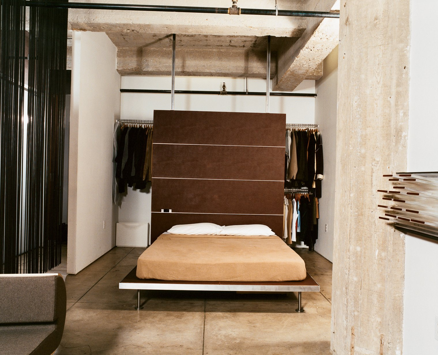 With a push of the sliding door, the bedroom morphs into an extension of the living room, adding much-appreciated square feet during dinner parties and other gatherings. The platform bed and backrest are both Tag Front designs. Tagged: Bedroom, Bed, and Concrete Floor.  Photo 6 of 9 in Cutting Up a Mini Loft in Los Angeles