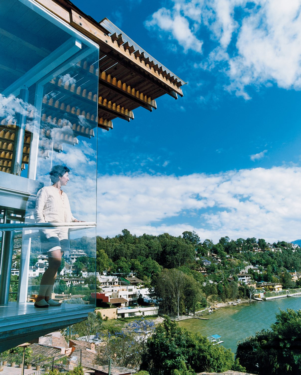 For his lakeside retreat just outside Mexico City, architect Bernardo Gomez-Pimienta designed everything from the house to the chairs to the china. Here, his wife, Loredana Dall' Amico, checks out the view from the balcony.