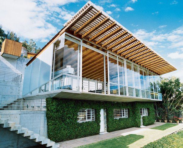 The house has what some architects would call an upside-down plan, with living spaces upstairs and bedrooms below. The upper story is strikingly transparent; the lower is camouflaged by thick, foliage-covered walls, which keep the sleeping areas cool.