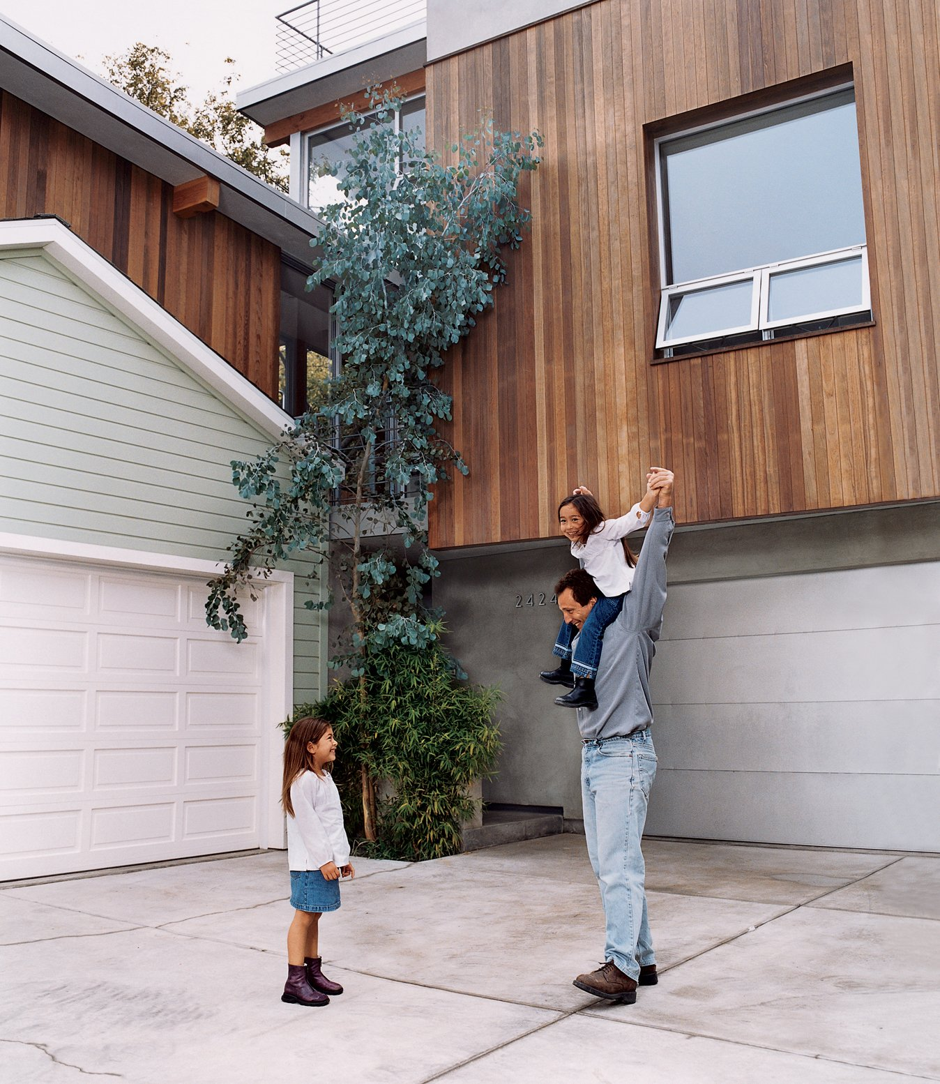 The architect with his daughters. The redwood strips on the new house were purposely cut to the same width as the horizontal wood siding on the old house to create visual harmony between the two. Tagged: Outdoor and Concrete Patio, Porch, Deck.  Photo 6 of 13 in Two Houses Are Better Than One