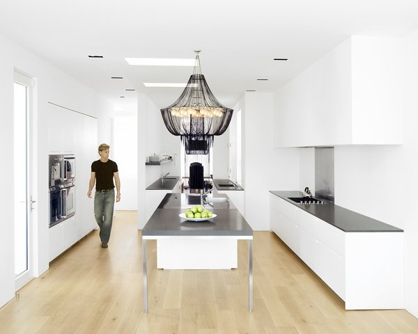 Hollis designed the kitchen--which features a Boffi kitchen system and Gaggenau appliances-- as three zones. The first centers around the stainless-steel-and-Zodiac-stone island, which is topped by a custom beaded chandelier by South African company TeamTwo Design. This zone functions as a place for food preparation, cooking, serving, and socializing. The second zone is the clean-up area, and the third is the bar.Photo by <br><br>Ben Mayorga Photography