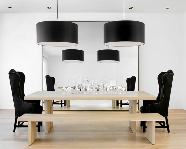 The kitchen opens up to the dining room, where Hollis played with size and shape. She designed the solid French oak dining table and bench, which were fabricated by B Serota Furniture and Architectural Design, and flanked the table with a Host and Hostess chair from Coup d'Etat San Francisco. She hung two Piet Boon-designed drum pendants over the table and placed a large mirror on the wall to extend the space so that the person sitting on the bench can see the living room fireplace in the reflection.Photo by <br><br>Ben Mayorga Photography