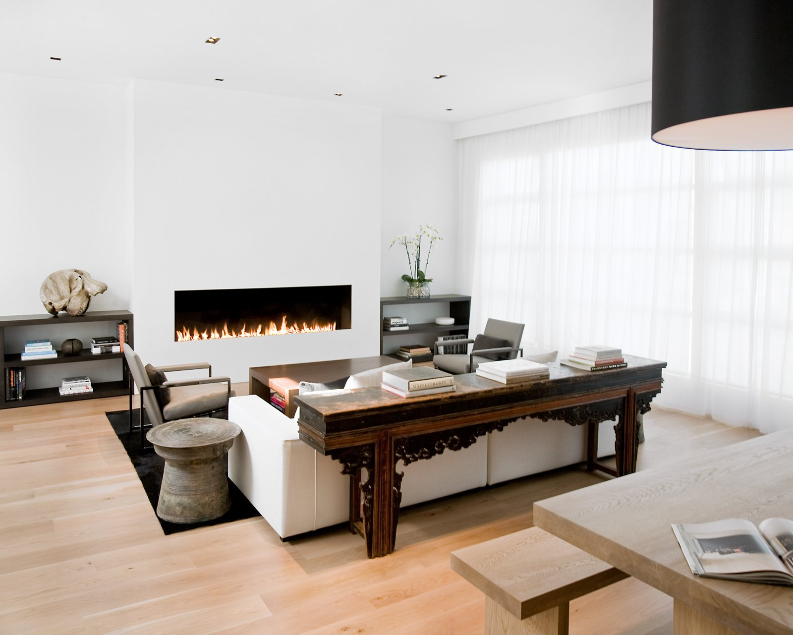 The living room and dining room were originally separated by a central fireplace, which Hollis removed to create this great room. She installed a custom eight-foot-long open gas fireplace in the living room (equipped with sensors that automatically turn it off when someone gets too near to the flames).Photo by   Ben Mayorga Photography  97+ Modern Fireplace Ideas by Dwell from Pacific Heights Remodel