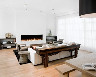 The living room and dining room were originally separated by a central fireplace, which Hollis removed to create this great room. She installed a custom eight-foot-long open gas fireplace in the living room (equipped with sensors that automatically turn it off when someone gets too near to the flames).Photo by <br><br>Ben Mayorga Photography