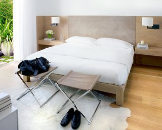 The master suite was relocated from the upper level to the lower level to separate public and private spaces. Hollis designed the custom white-oak bed and suite headboard with built-in bedside tables (fabricated by B Serota Furniture and Architectural Design and upholstered by Kroll Furniture) and opened the room to the backyard garden to extend the space.Photo by <br><br>Ben Mayorga Photography