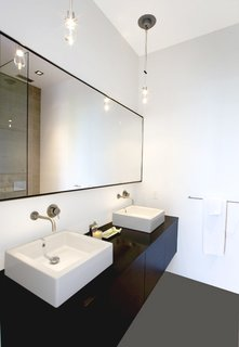 Pacific Heights Remodel - Photo 9 of 10 - In the master bathroom, Hollis designed a custom floating oak vanity with two sinks, outfitted with Boffi fixtures.Photo by <br><br>Ben Mayorga Photography