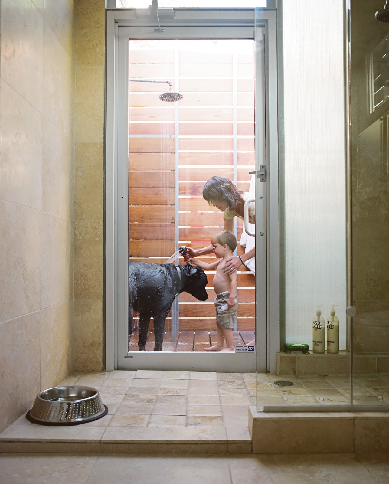 A door in the master bathroom connects the indoor shower to an outdoor one. Here, Feldmann and the couple's three-year-old son, Eli, wash their dog Arnold--named by the previous owner after the local St. Arnold Brewing Company. Tagged: Outdoor and Shower Pools, Tubs, Shower.  Photo 2 of 22 in The Shipping Muse