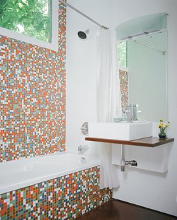 Robertson--with the help of developers Katie Nichols and John Walker, who were heavily involved in the design process--finished the guest bathroom with Modwalls tiles and a sink they found on eBay. They used a piece of marine plywood, leftover from building the front-porch steps, to create a counter on which the sink could sit--and where the family can rest their toothbrushes. To the right of the sink is a Toto dual-flush toilet, which is great for conserving water but has proven problematic for toilet training, as American potty seats aren't designed to fit these Japanese basins.
