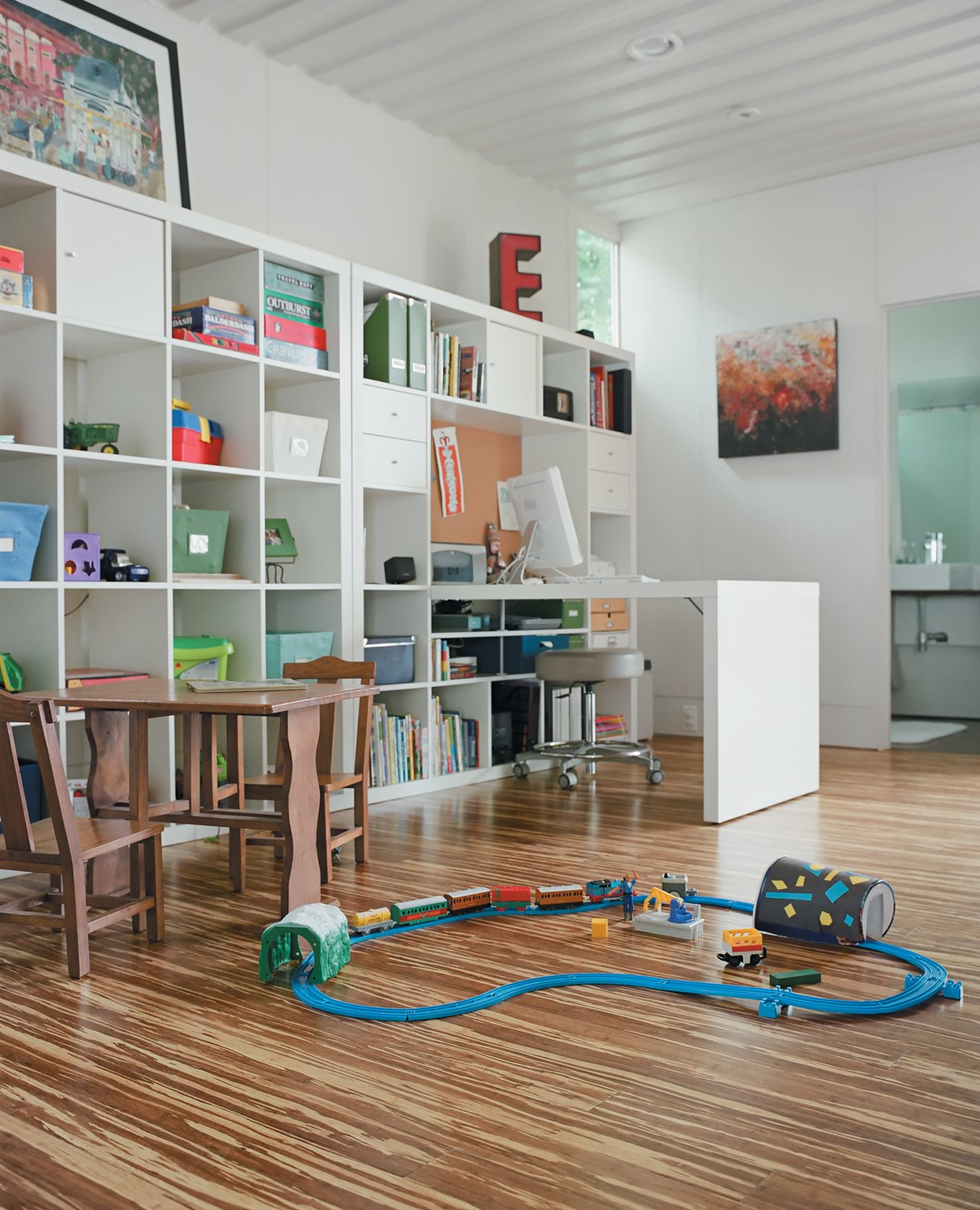 """In the cutout of the 40-foot-long container along the northern side of the house is the office and play area. It's a mix of new and old: The bookcase and desk are from Ikea's Expedit living room storage collection while the small table and chairs were made by Freeman's grandfather. """"He was a furniture maker and would make one piece for each of the 13 grandkids each year,"""" Feldmann says. Tagged: Kids Room and Playroom.  Photo 4 of 22 in The Shipping Muse"""