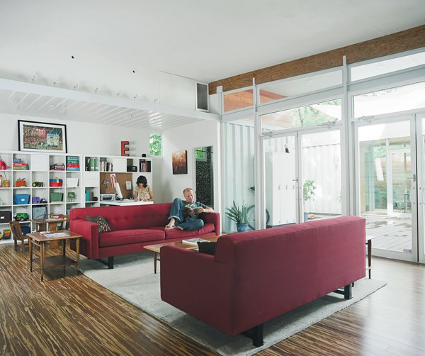 """The open-plan living spaces act like a """"giant kitchen"""" that invites guests to mingle throughout the house. Fresh white light gets the bookend treatment with parallel ruby sofas. You'd never know this home is made from shipping containers—unless you look twice. See more."""
