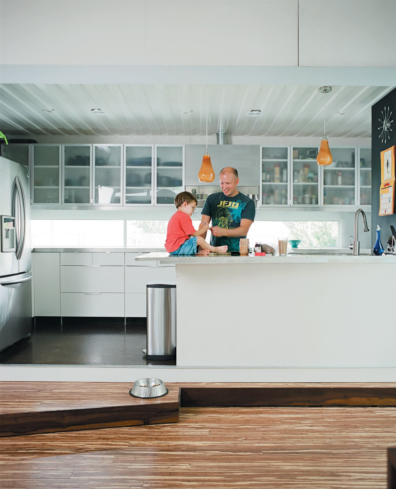 In the kitchen proper, Freeman fixes a snack while son Eli plays on the counter, one of his favorite spots in the house, second only to the kitchen steps. Tagged: Kitchen and White Cabinet.  Shipping Containers by Dwell from The Shipping Muse