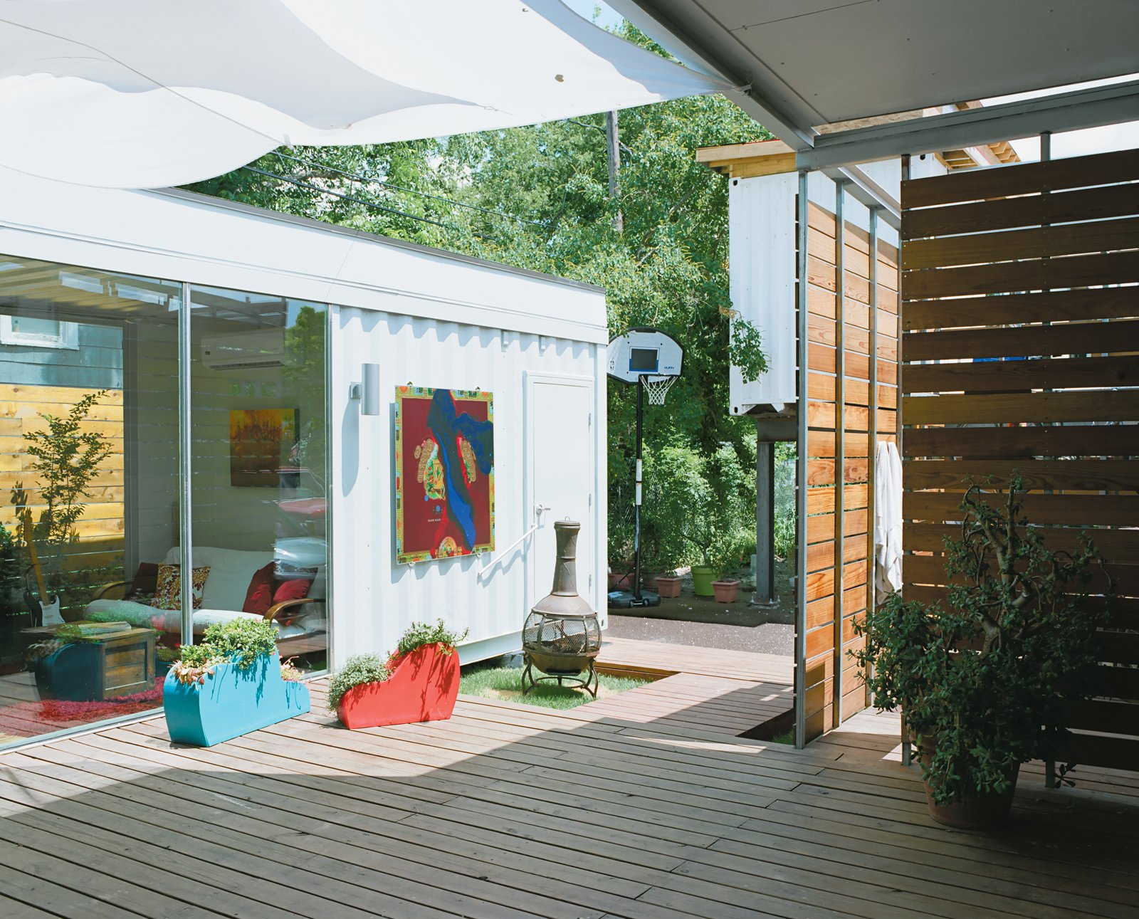 """The 400-square-foot deck between the main house and guest quarters catches a cool breeze—a big bonus during Houston's """"super-summers""""—and is often filled with the couple and their friends enjoying local microbrews. """"The challenge was how to stitch together the house and the guest container without it looking like at the last minute we decided we needed a little more space,"""" Robertson says."""