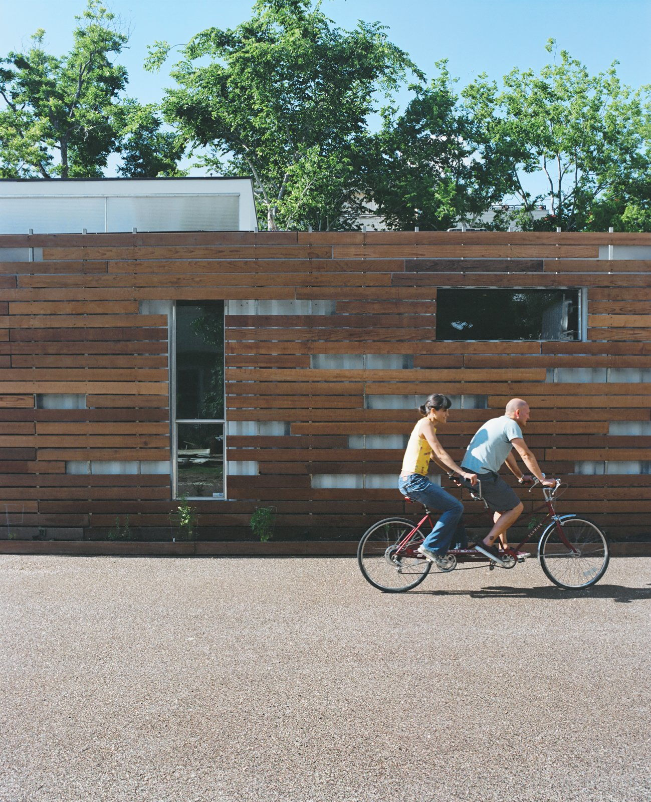 Alongside the redwood shade screen, which keeps the house from overheating, Freeman and Feldmann grow vegetables in an 18-inch-wide garden but frequently bike to nearby eateries for the local Mexican cuisine. Tagged: Exterior, House, Wood Siding Material, Metal Siding Material, and Shipping Container Building Type.  Shipping Containers by Dwell from The Shipping Muse
