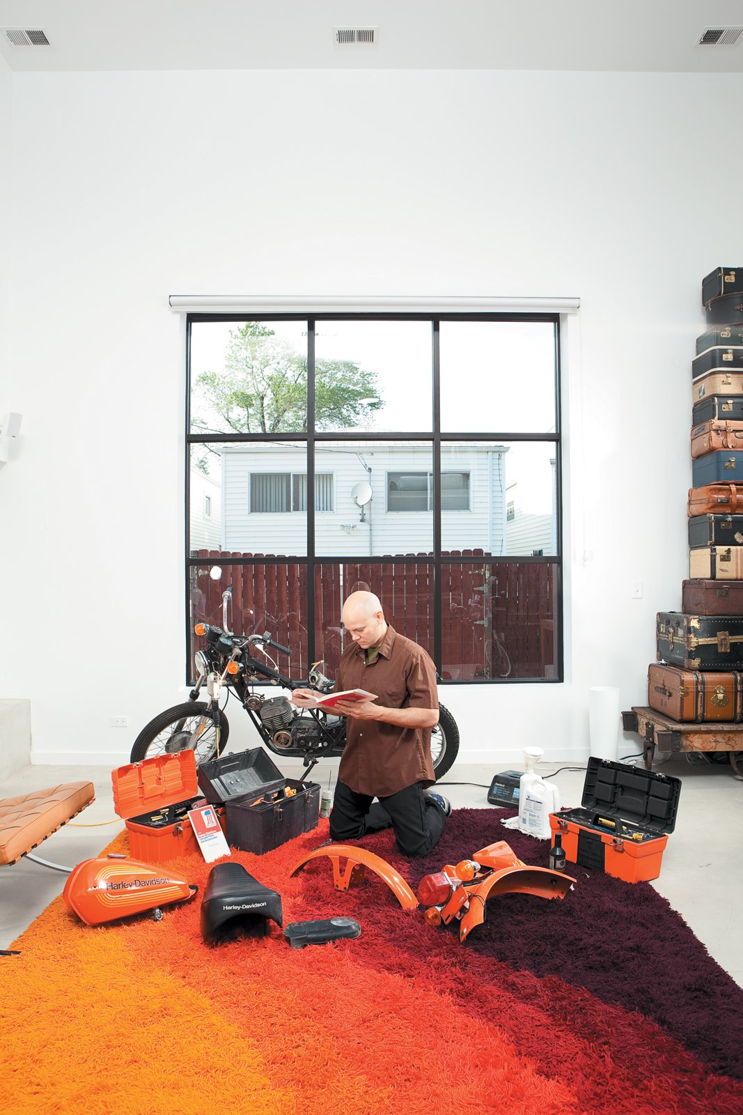 In the light-flooded living room, Hernandez does a little work on a 1976 Italian-made Harley-Davidson SXT125. Tagged: Living Room and Rug Floor.  Photo 9 of 10 in The Brick Weave House in Chicago