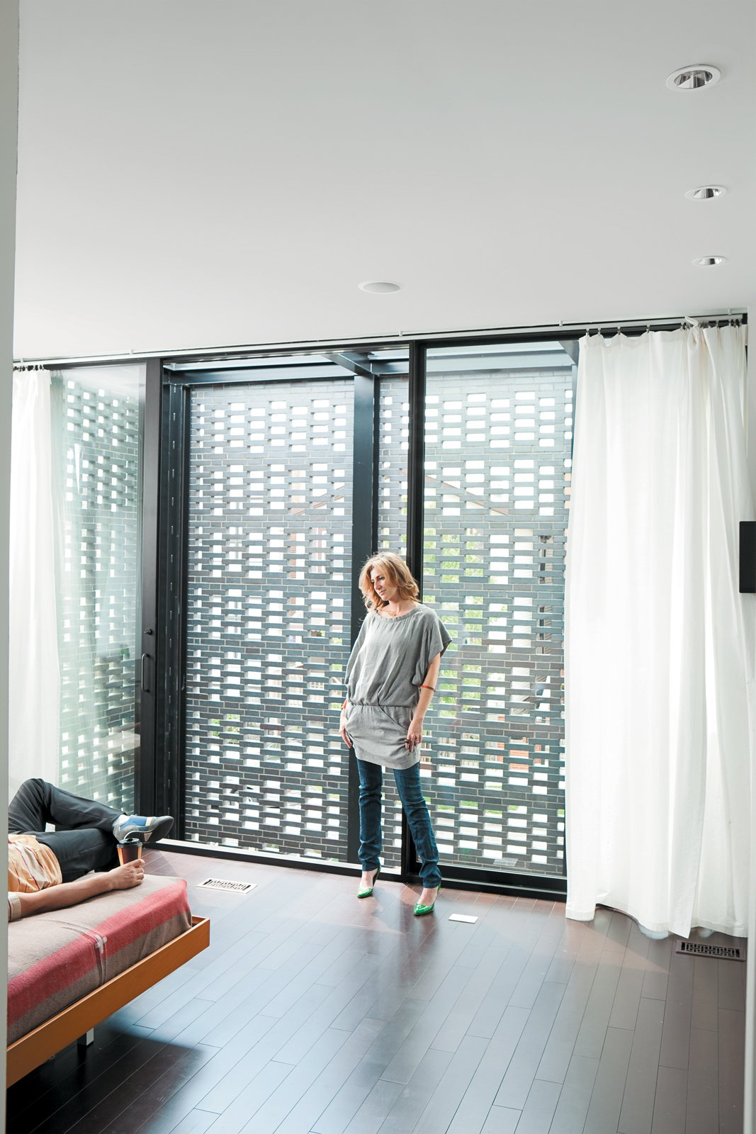 In the master bedroom, the couple enjoy the ample natural light that filters through the brick screen. Tagged: Bedroom, Bed, and Dark Hardwood Floor.  Photo 6 of 10 in The Brick Weave House in Chicago