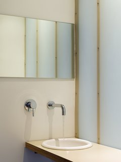 Because the upper-level bathroom is in the middle of the upper level, without a window, Willmer and her team--including designers Kathleen Heimerman and Joseph Barajas--created one wall with a translucent material to bring a lightness and glowing affect to the room. <br><br>Photo by Ken Gutmaker