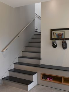 "Entering the home through the garage, the rest of the house is accessed through the mudroom, which leads up the stairs to the public level or straight through to the bedrooms and backyard beyond. The third stair from the bottom extends into a bench for putting on and taking off shoes. ""It was a nice opportunity to make the stairs sculptural and integrated into the space,"" Willmer says.<br><br>Photo by <br><br>Ken Gutmaker"