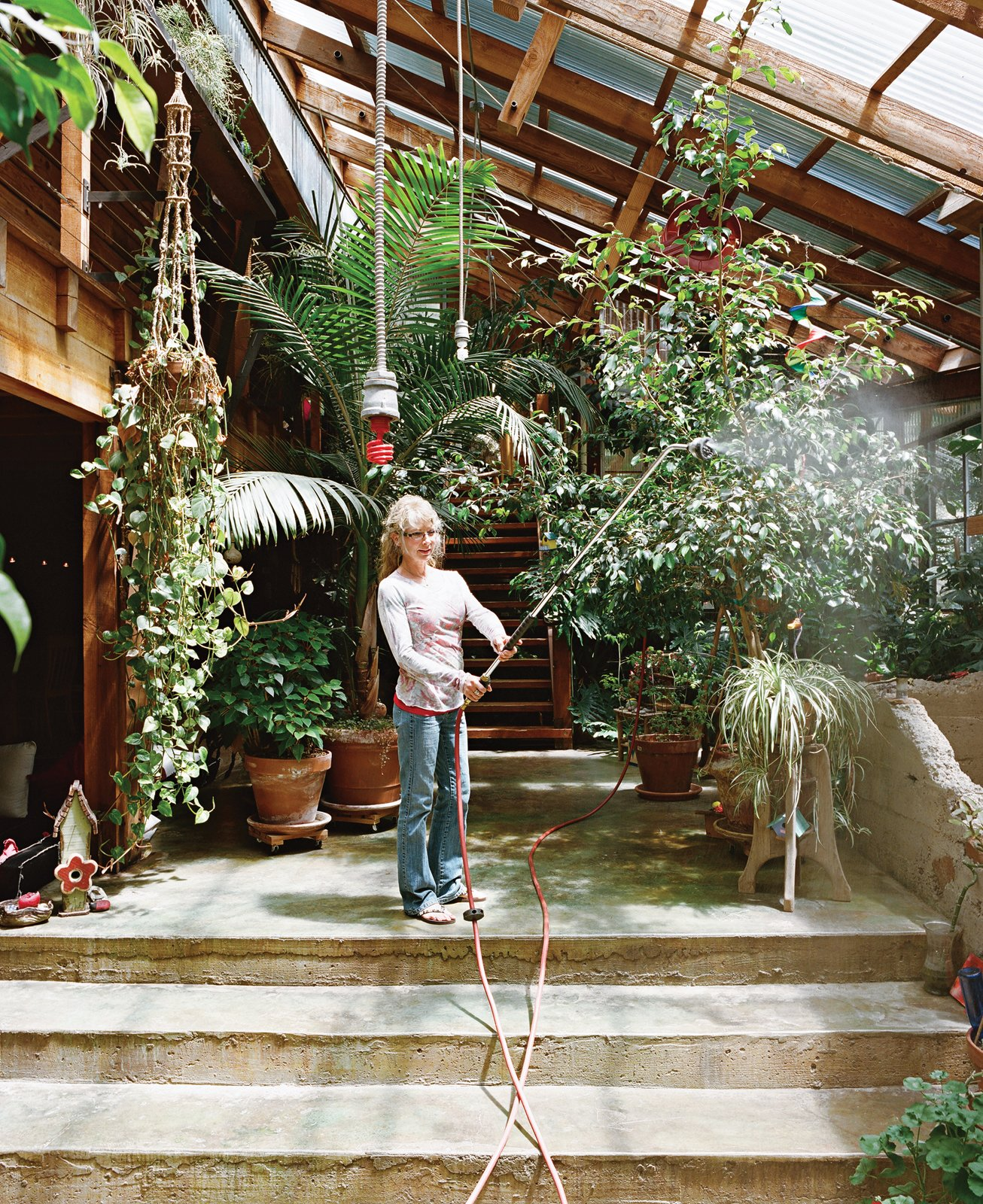 Sue waters the indoor foliage with an industrial hose hung from the ceiling.  Photo 5 of 13 in Diamond in the Rough (and Ready)