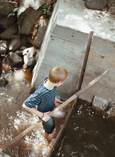 The young Meffans relish playing in the creek's adjustable dam, made from poured concrete. The nutrient-rich silt that collects over the summer is dumped on the vegetable garden in the winter, when the creek flows freely.