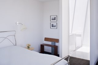 Noe Valley Renovation - Photo 5 of 17 - Back in the master bedroom, the designers installed Tolomeo wall sconces by Artemide next to the bed and placed a bench next to the door made by Hart's uncle, Peter Czuk of Czuk Studio. The bedroom door, which is rarely closed, is the starting point for the continuous flow of movement and light from the top of the house to the main level and down to the bottom floor.<br><br>Photo by <br><br>Sharon Risedorph