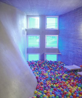 The meditation-room-turned-ball-pit, illuminated by blue tinted windows.