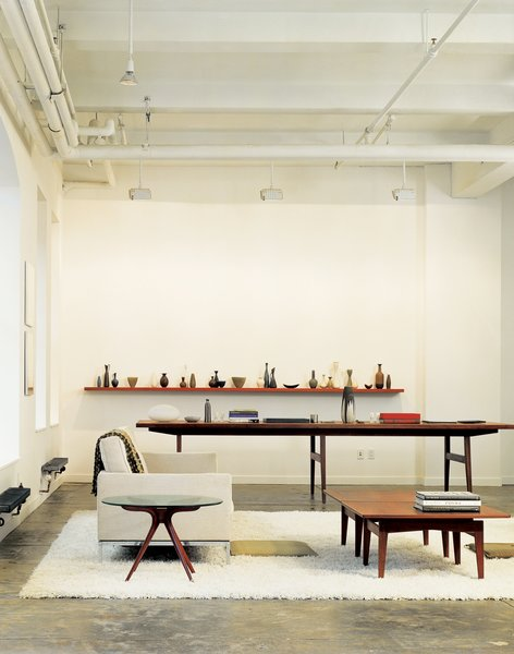 """The oversize conference table in Bob Weinstein's live/work loft (like the cocktail table in the foreground) was designed by Jens Risom, and, he says, """"supposedly came from the conference room of the Kinney Shoe Corporation."""" Weinstein uses the table to display part of his Scandinavian pottery collection."""