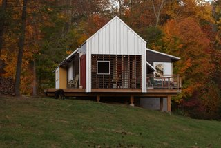 Farmhouse Redux - Photo 1 of 13 - Red and yellow accent colors blend with natural North Carolina foliage. Cantilevered porches and decks provide deep shadows. Image courtesy Chad Everhart Architect.