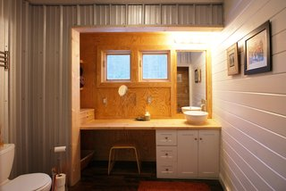 "Farmhouse Redux - Photo 7 of 13 - The vanity in the bath is housed in what Chad calls a ""bump-out"" or a saddlebag, a feature that expands interior space by a few feet on either side of the farmhouse. Image courtesy Chad Everhart Architect."