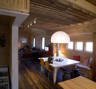 Farmhouse Redux - Photo 9 of 13 - The ceiling was dropped over the dining room to provide a more intimate setting. Strips of salvaged hemlock and chestnut wrap the interior wall and ceiling. A loft for naps and overnight guests is above. Image courtesy Chad Everhart Architect.