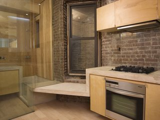 Domestic Ribbon - Photo 5 of 9 - The kitchen has a Miele cooktop, oven and hood, as well as a small seat before a double-hung window, one of very few natural light sources in the apartment. The concrete ribbon continues into the adjacent bathroom, becoming part of the bathtub and counter. Image courtesy Brian Riley.