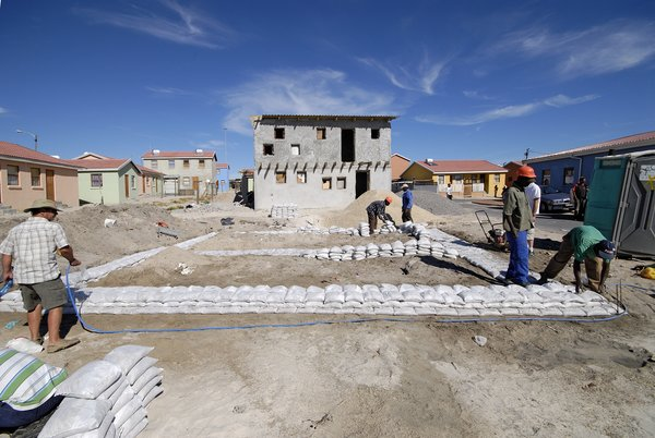 Before building the framework of the house with pine timber and galvanized metal, the workers piled sandbags on the ground to map out the home's foundation. Image courtesy Interactive Africa/ Design Indaba