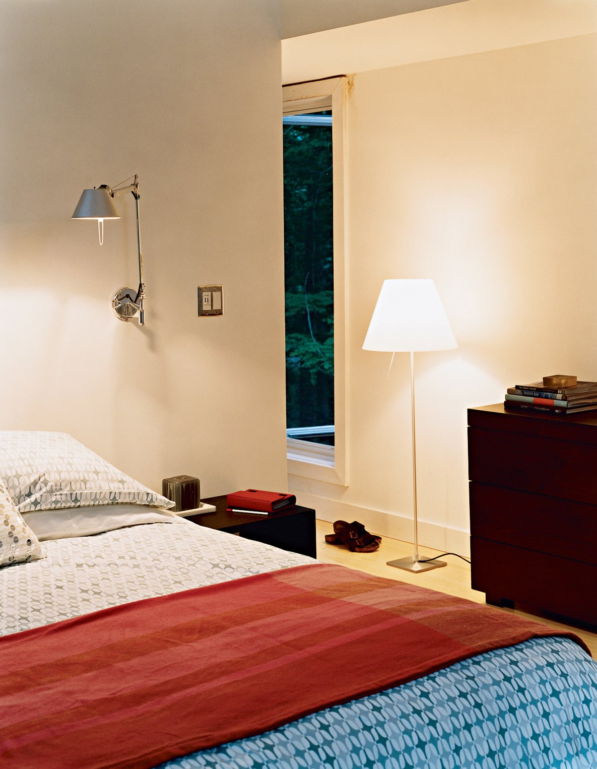 The master bedroom has a number of windows in varying shapes and sizes, providing unique views to the woods outside. The bed, chest of drawers, side tables, and geometric linens are all from West Elm. The Tolomeo wall lamps are by Artemide. Prefab, Proven - Photo 6 of 12