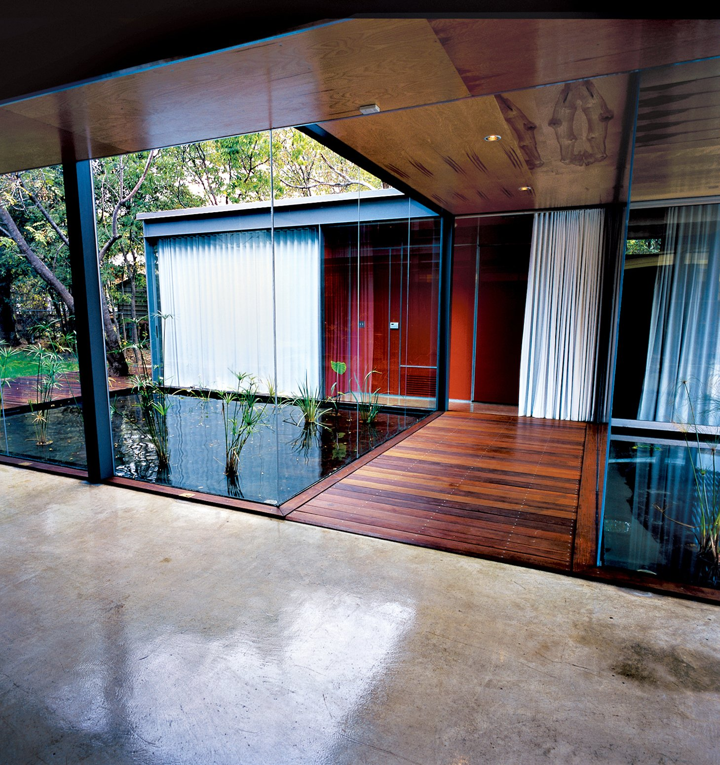 """The exterior walls of the Bercy house are constructed with Thermasteel, panels made from galvanized steel and a unique resin that provide structural framing, insulation, and vapor barrier with an R-29 rating twice the required amount. """"We have so much glass that we have to offset it by having very efficient ceiling and wall systems,"""" says Bercy. """"We wanted movable glass walls instead of tiny little sliding glass doors that pop off their tracks all the time,"""" says Bercy. So he and Chen tracked down the double-glazed, insulated, six-by-nine-foot doors rom a company called Fleetwood. """"They're a little more expensive, but when you slide the heavy doors open, you're making a profound gesture to leave the house and step outside,"""" says Bercy. The word """"doorknob"""" isn't used much around the house for the simple reason that there aren't any. """"We didn't want to clutter the house up with traditional hardware,"""" says Bercy. Instead, they used pulls found in boats that lie flush when not in use so that the doors become hinged extensions of the walls—the idea being that the door disappears and the core appears continuous."""