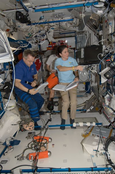 Canadian Space Agency astronaut Robert Thirsk and NASA astronaut Nicole Stott, both Expedition 21 flight engineers; along with European Space Agency astronaut Frank De Winne (background), commander, work in the Harmony node of the ISS. Photo taken October 15, 2009. Image courtesy of NASA.